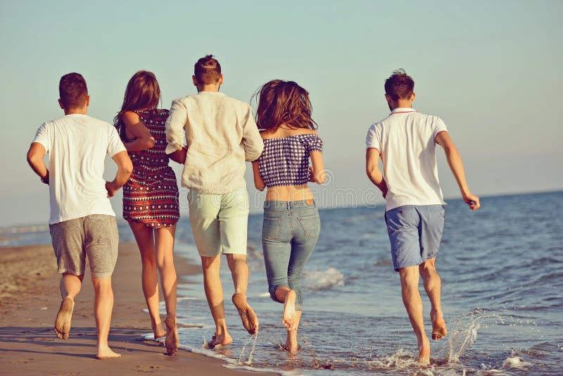 Vänner som är roliga på stranden under solnedgångsolljus arkivfoton