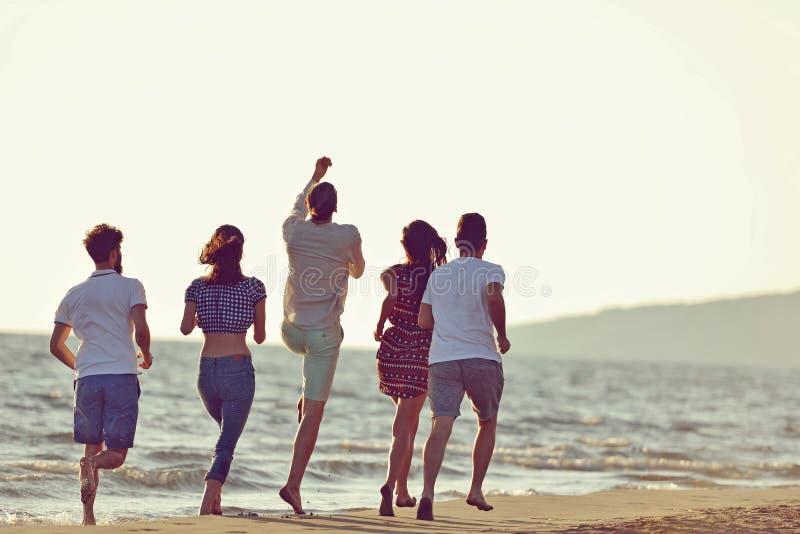 Vänner som är roliga på stranden under solnedgångsolljus arkivfoto
