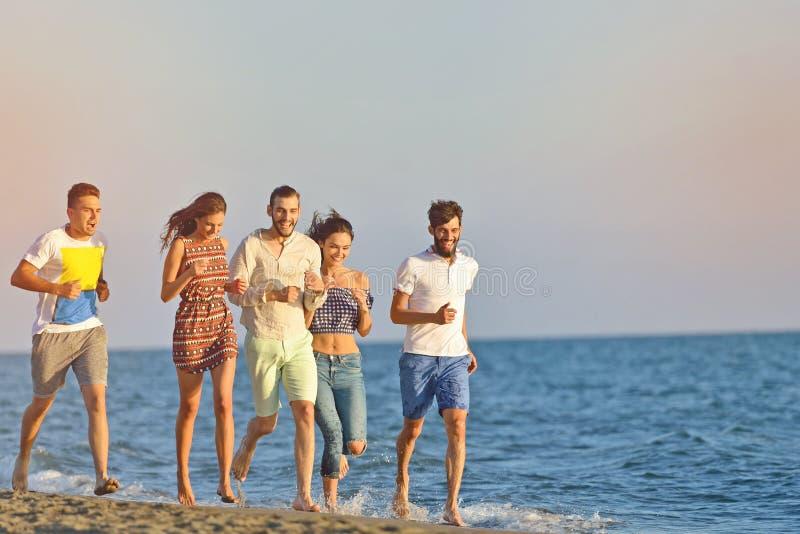 Vänner som är roliga på stranden under solnedgångsolljus royaltyfri bild