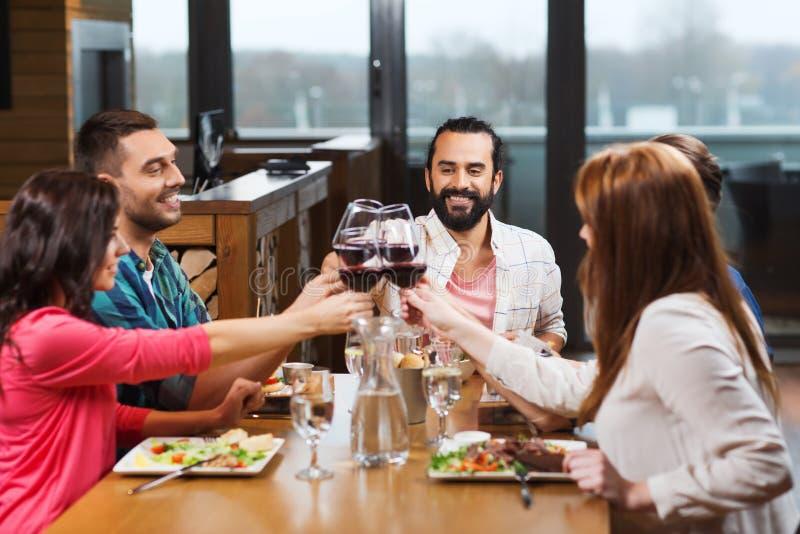 Vänner som äter middag och dricker vin på restaurangen royaltyfria bilder