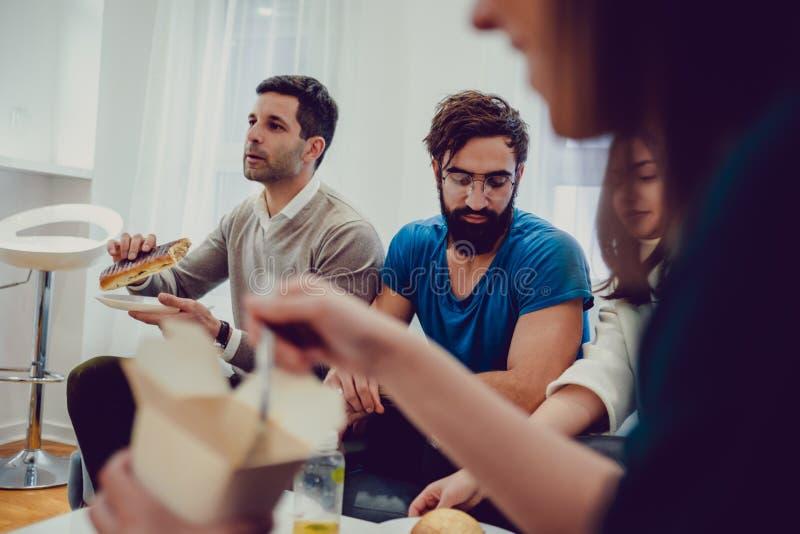 Vänner som äter och talar i vardagsrummet arkivfoton
