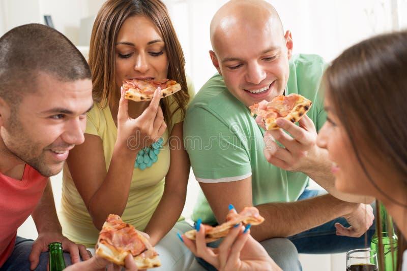 Vänner som äter pizza royaltyfri bild