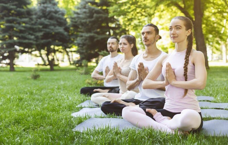 Vänner som öva yoga parkerar in, framställning av gesten av namaste royaltyfri bild
