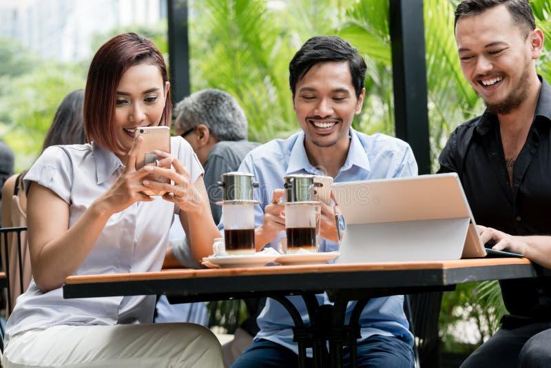 Vänner som använder apparater, förband till den trådlösa internet av en modern coffee shop royaltyfria foton