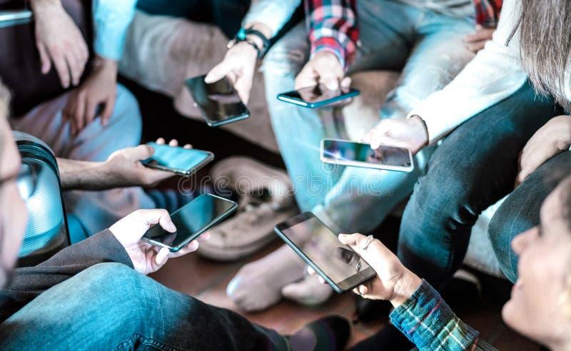 Vänner som använder sig av roliga mobiltelefoner hemma - Stäng av personer som delar foton på sociala medienät royaltyfri foto