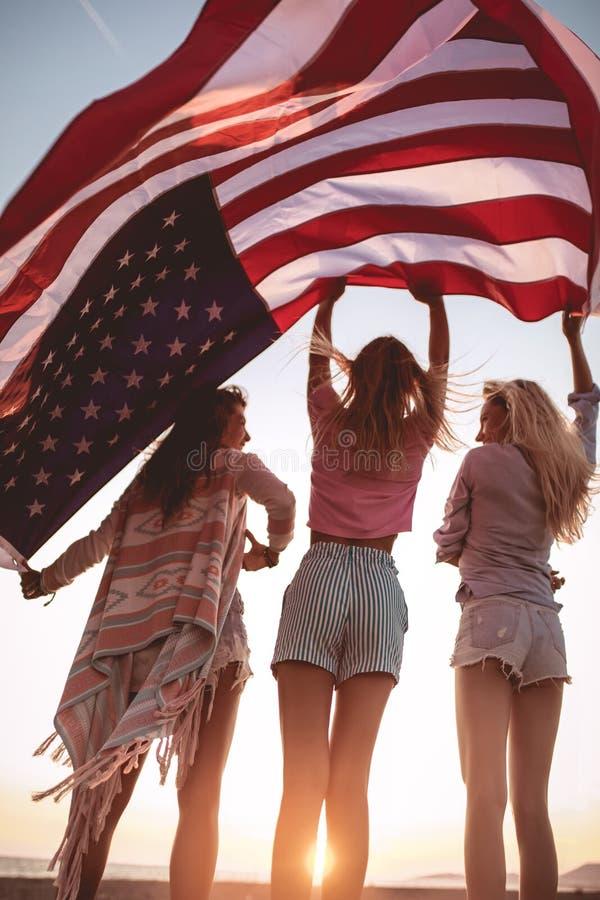 Vänner som bär amerikansk flagg på stranden royaltyfri bild
