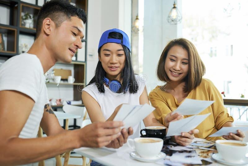 Vänner som diskuterar foto i kafé royaltyfria bilder
