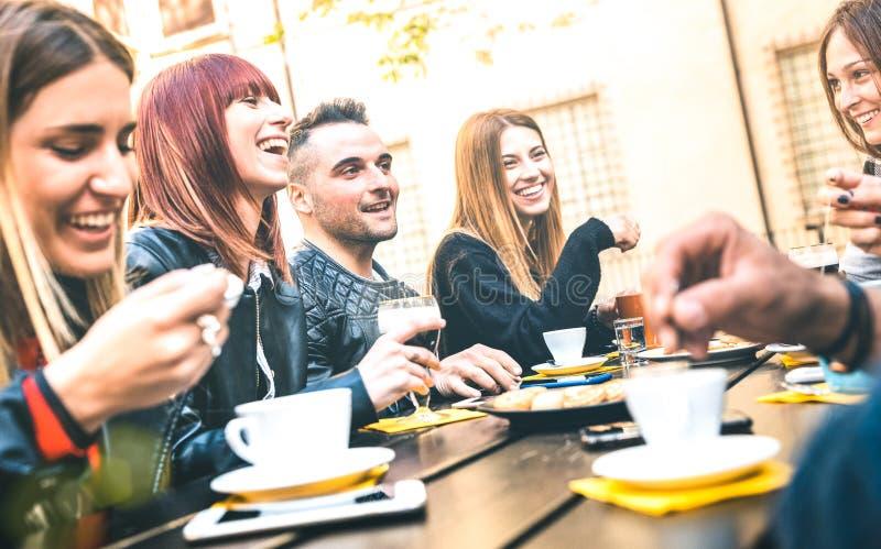 Vänner som dricker cappuccino på kafferestaurangen - Millenial folk som tillsammans talar och har gyckel på modestångkafeterian arkivfoto