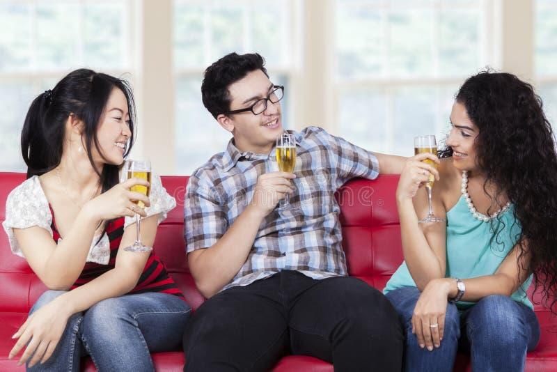 Vänner som dricker champagne på soffan royaltyfria foton