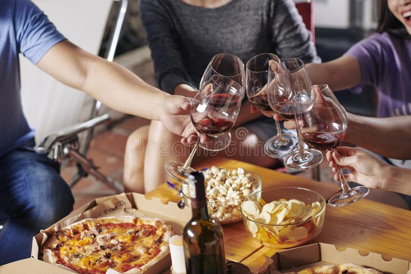 Vänner som dricker vin på partiet royaltyfri bild