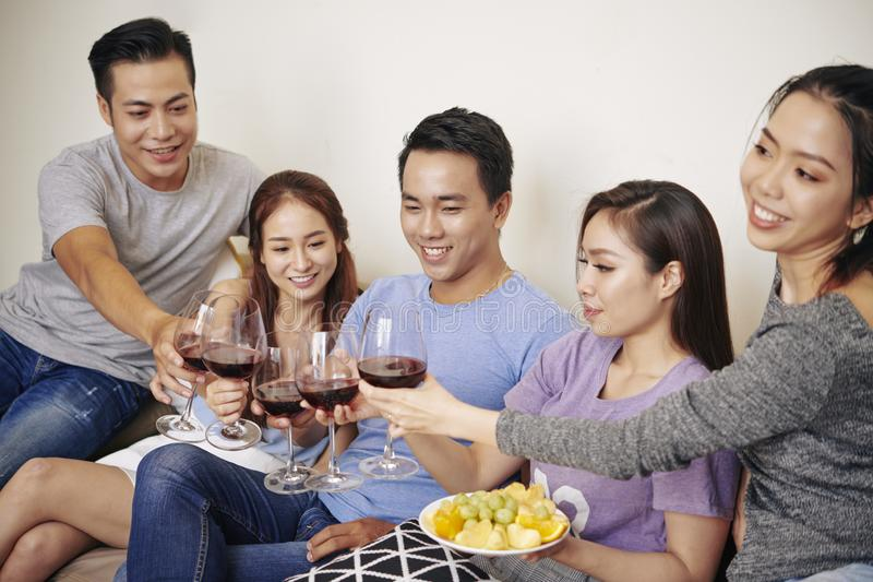 Vänner som dricker vin på partiet royaltyfri foto