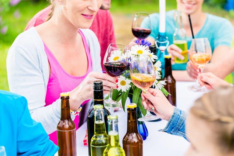 Vänner som firar det lilla trädgårds- partiet som klirrar exponeringsglas fotografering för bildbyråer