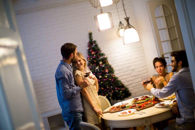 Vänner som firar helgdagsafton för jul eller för nytt år royaltyfri fotografi