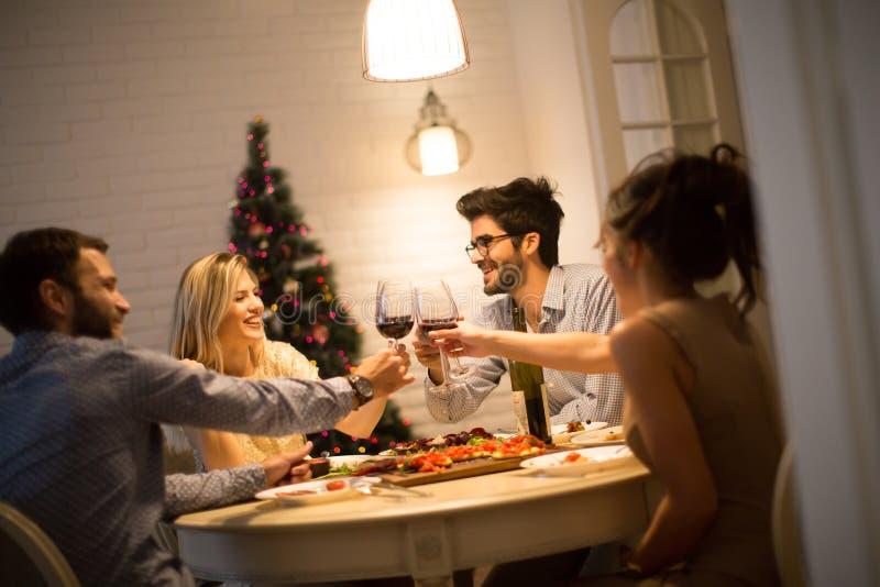Vänner som firar helgdagsafton för jul eller för nytt år royaltyfri bild