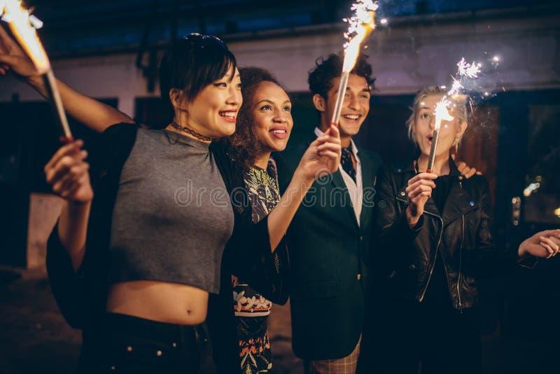 Vänner som firar helgdagsafton för nya år med fyrverkerier royaltyfria foton