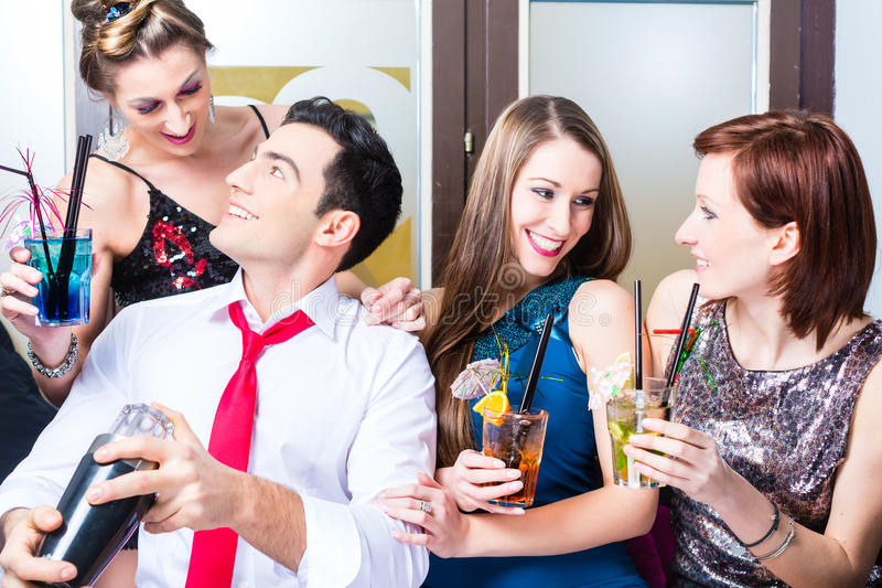 Vänner som firar med barkeeperen i coctailstång royaltyfria foton