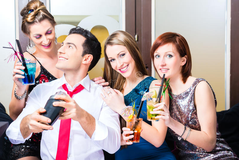Vänner som firar med barkeeperen i coctailstång arkivfoton