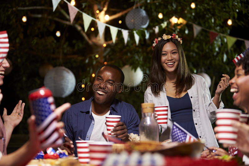 Vänner som firar 4th av Juli ferie med trädgårdpartiet arkivfoton