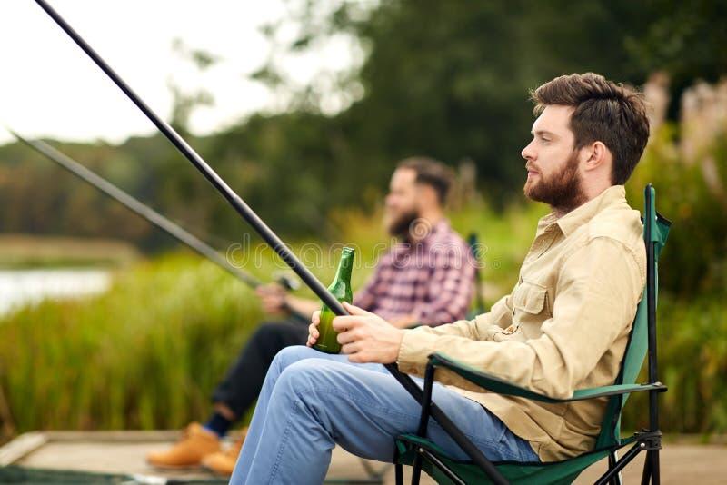 Vänner som fiskar och dricker öl på sjön royaltyfri foto