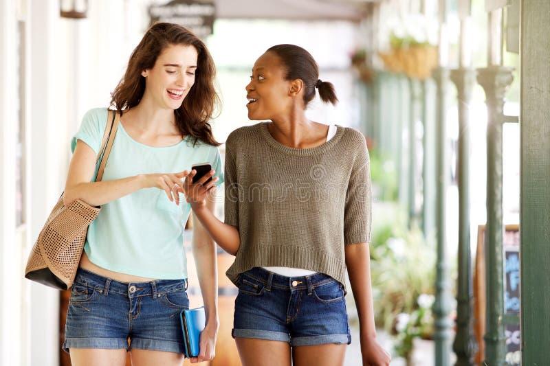 Vänner som går tillsammans genom att använda mobiltelefonen royaltyfria foton