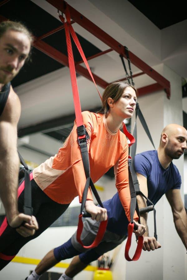 Vänner som gör övningar i en idrottshall med remmar arkivfoto