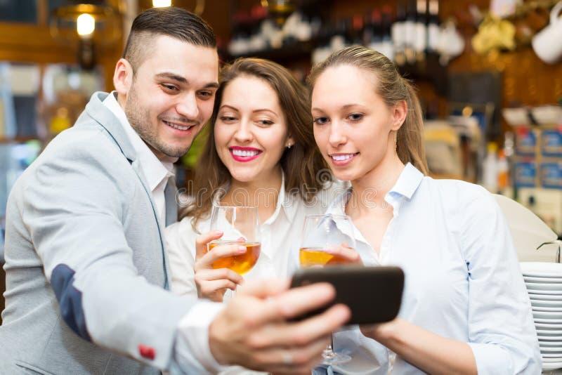Vänner som gör bilder genom att använda smartphonen arkivfoton