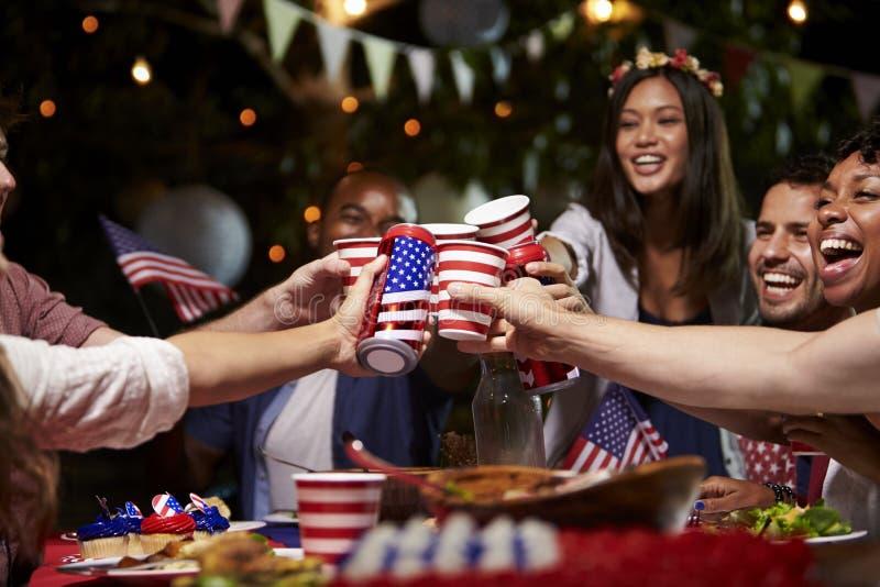 Vänner som gör ett rostat bröd för att fira 4th av Juli ferie royaltyfri foto