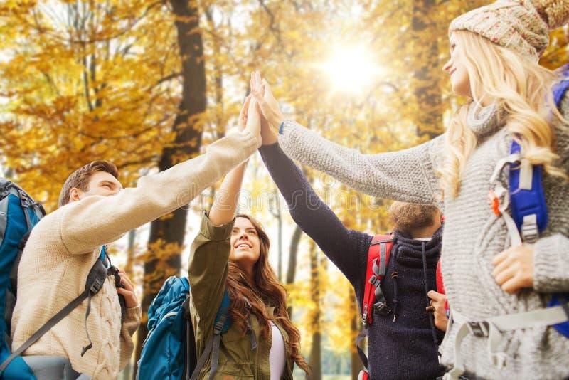 Vänner som gör högt fem på vandring i höst fotografering för bildbyråer