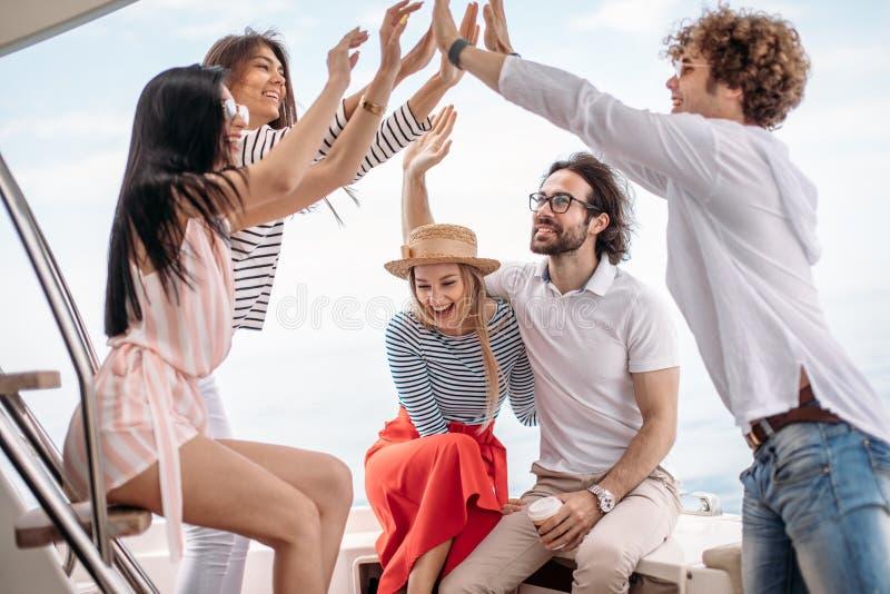 Vänner som gör partiet på en yacht och att ha ett utsmyckat parti på ett lyxigt fartyg fotografering för bildbyråer