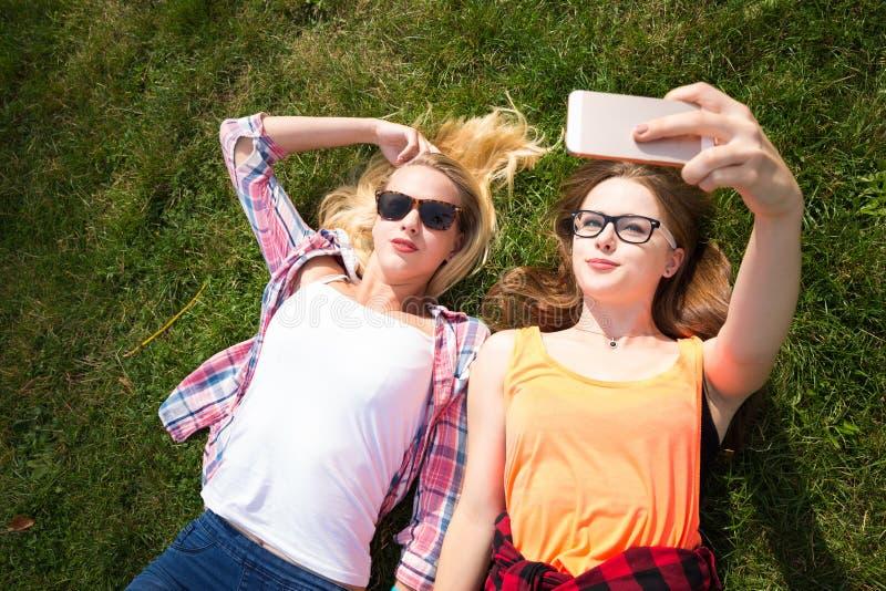 Vänner som gör selfie och har gyckel parkerar in Lyckliga tonårs- flickor spenderar tid tillsammans i staden royaltyfria foton