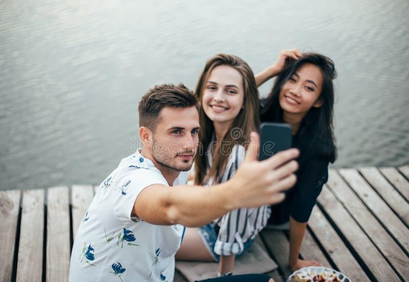 Vänner som gör selfiesammanträde på pir med sjöbakgrund medan royaltyfri fotografi
