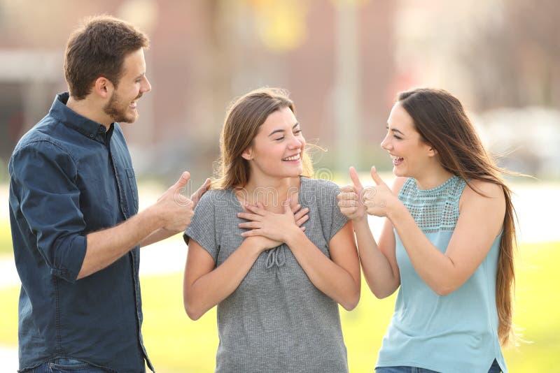 Vänner som gratulerar en lycklig flicka i gatan royaltyfri bild