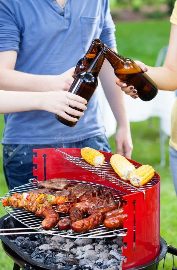 Vänner som grillar och dricker öl royaltyfria foton