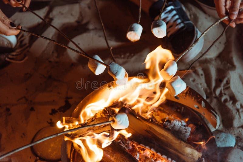 Vänner som grillar söta marshmallower på brasa royaltyfri foto