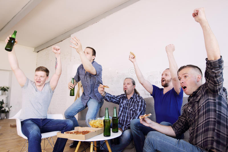 Vänner som håller ögonen på den vinnande fotbollsmatchen royaltyfri bild