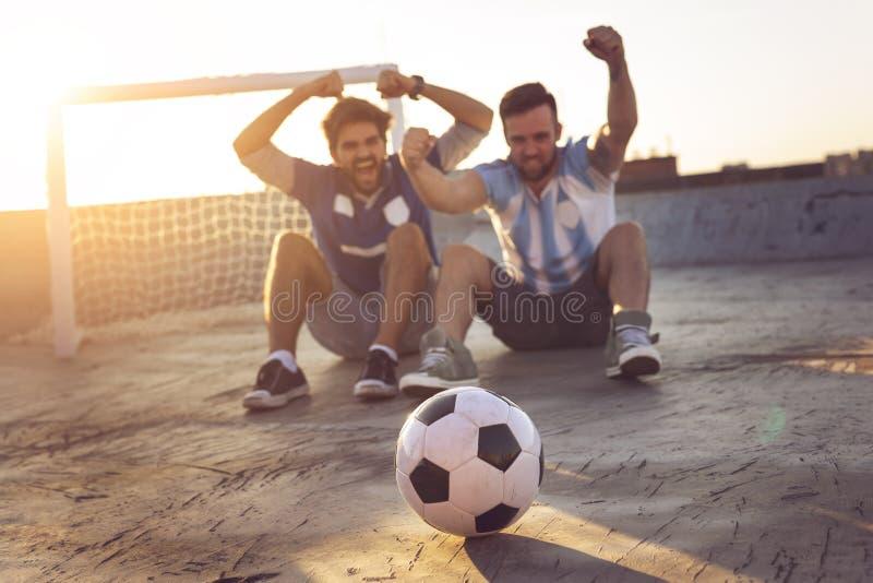 Vänner som håller ögonen på en fotbollsmatch arkivbilder