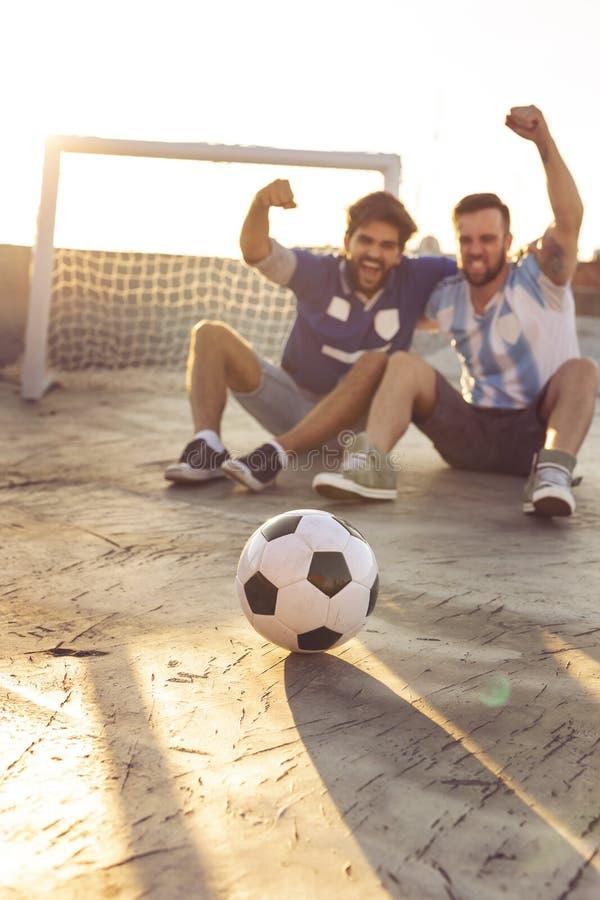Vänner som håller ögonen på en fotbollsmatch arkivfoto