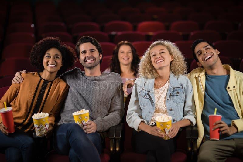 Vänner som håller ögonen på film royaltyfri fotografi