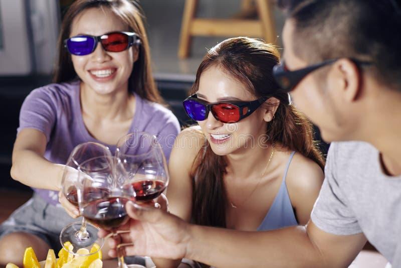 Vänner som håller ögonen på film och tillsammans dricker vin arkivbild