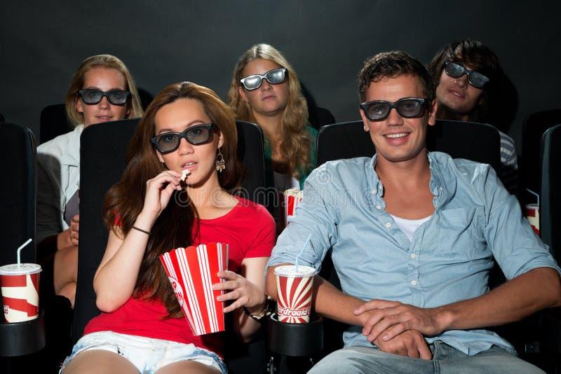 Vänner som håller ögonen på filmen 3D på bion royaltyfri bild