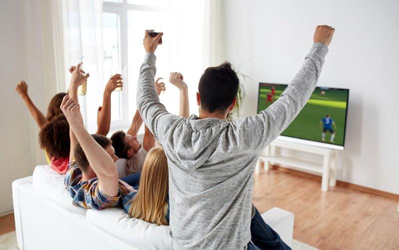 Vänner som håller ögonen på fotboll på tv och firar mål royaltyfri bild