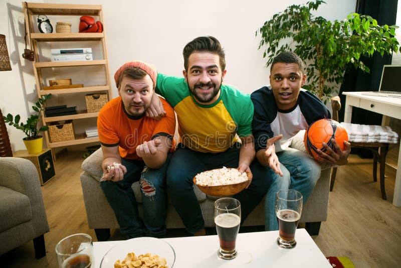 Vänner som håller ögonen på fotbollleken fotografering för bildbyråer