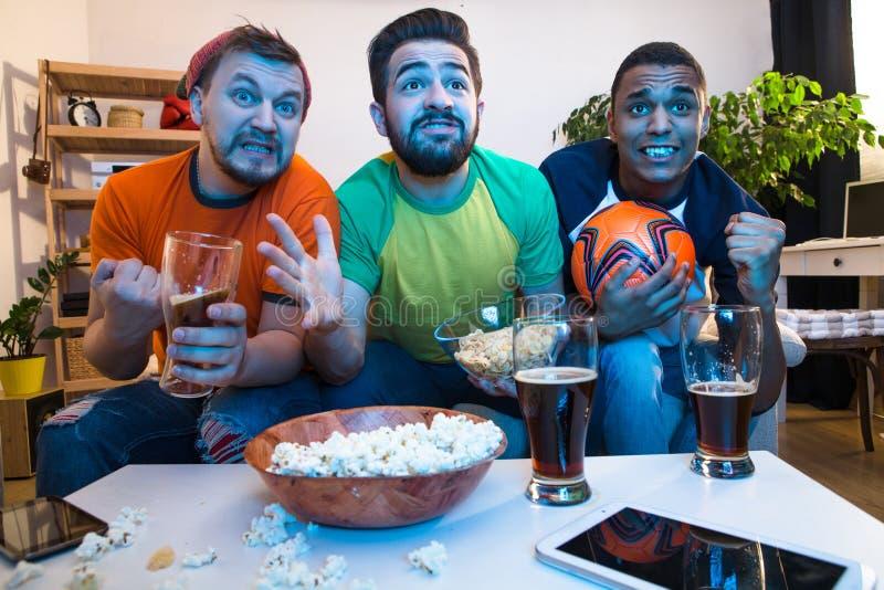Vänner som håller ögonen på fotbollleken royaltyfri fotografi