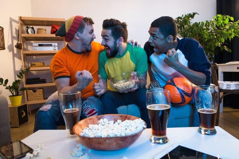 Vänner som håller ögonen på fotbollleken royaltyfria bilder