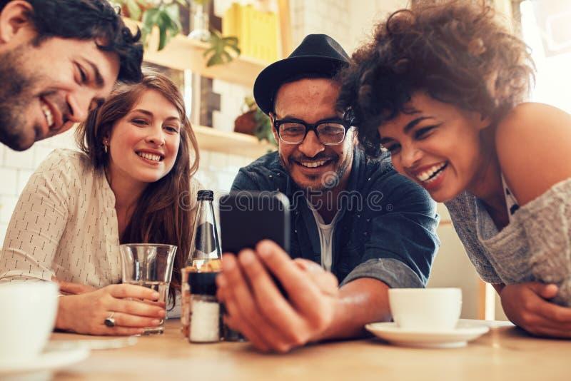 Vänner som håller ögonen på foto på mobiltelefonen royaltyfri fotografi
