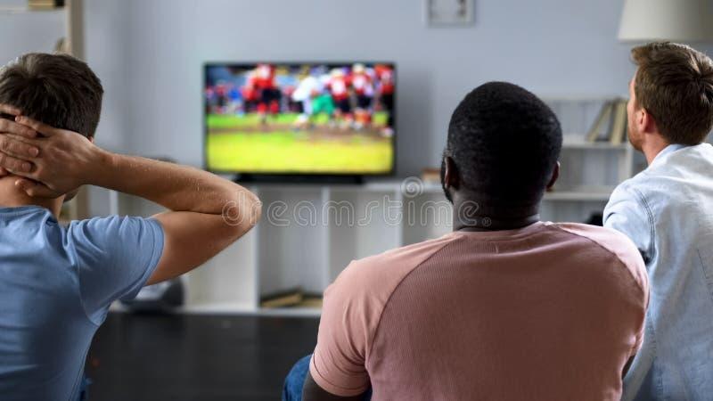 Vänner som håller ögonen på nervöst konkurrens för amerikansk fotboll på skärmen, soffaexperter arkivfoto