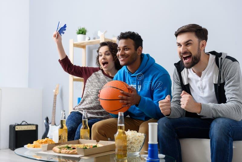 Vänner som håller ögonen på sporten på TV arkivfoto