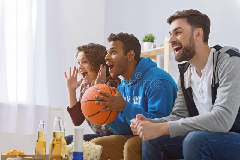 Vänner som håller ögonen på sporten på TV royaltyfria bilder