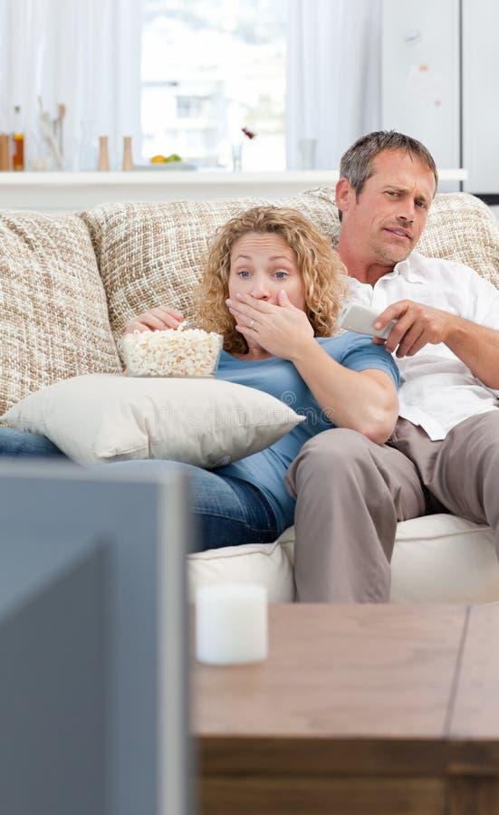 Vänner som håller ögonen på tv:n i vardagsrumet royaltyfria foton