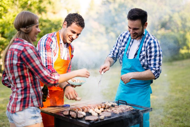Vänner som har ett grillfestparti i natur royaltyfria bilder